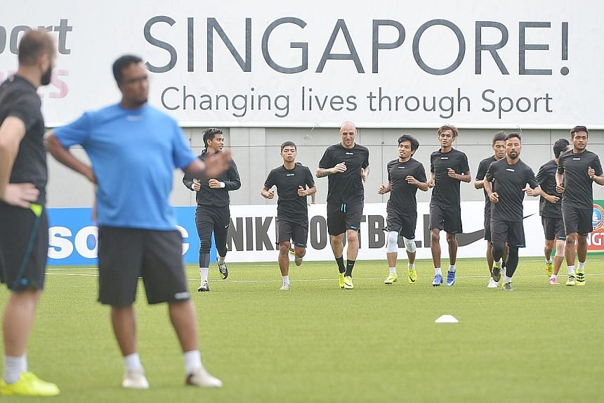 Tampines Rovers players preparing for their AFC Cup tie with Bengaluru FC at the Jalan Besar Stadium, while coach Akbar Nawas talks tactics with captain Fahrudin Mustafic. The Stags are looking to overturn their one-goal deficit from the first leg in