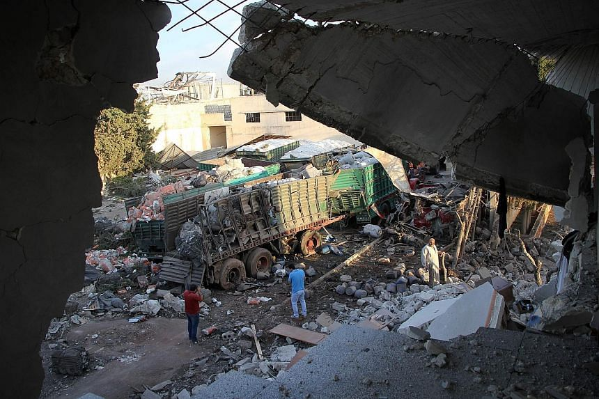 Cargo from aid trucks strewn on the ground in Orum al-Kubra on the outskirts of the northern Syrian city of Aleppo yesterday, the morning after a convoy taking humanitarian assistance to the town was hit by an air strike. The United Nations said at l
