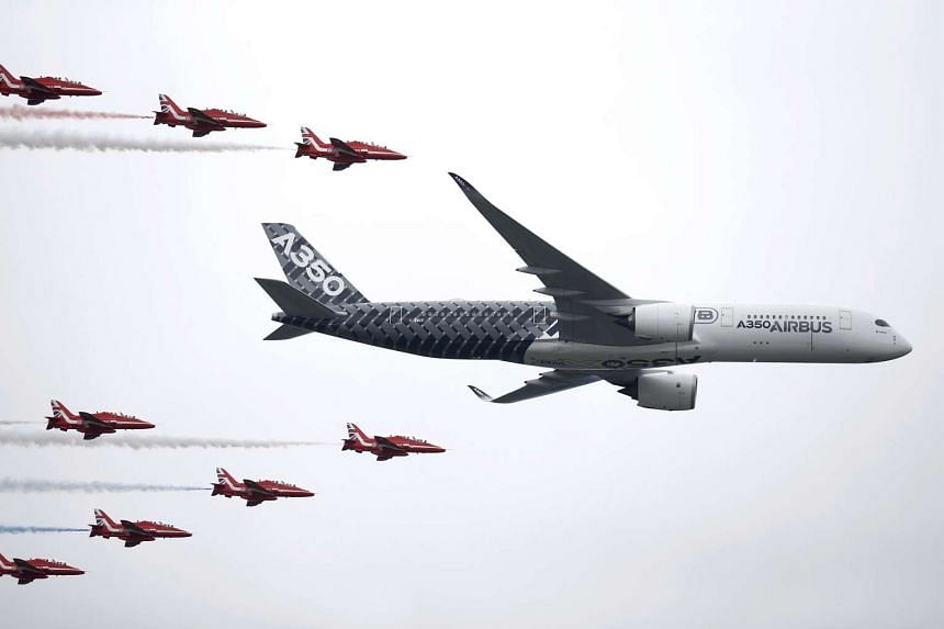 An Airbus A350 flies in formation with Britain's Red Arrows flying display team at the Farnborough International Airshow on July 15, 2016.