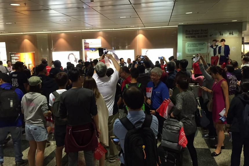 Supporters gather at Changi Airport to welcome home Singapore's Paralympians.