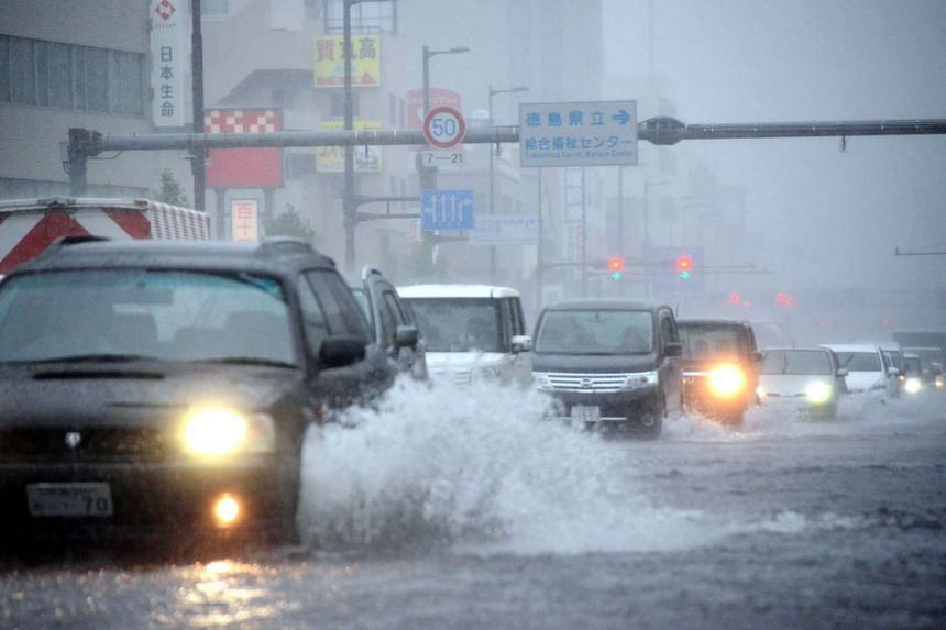 Vehicles drive through a flooded street as Typhoon Malakas moves across Tokushima, Japan, on Sept 20, 2016.