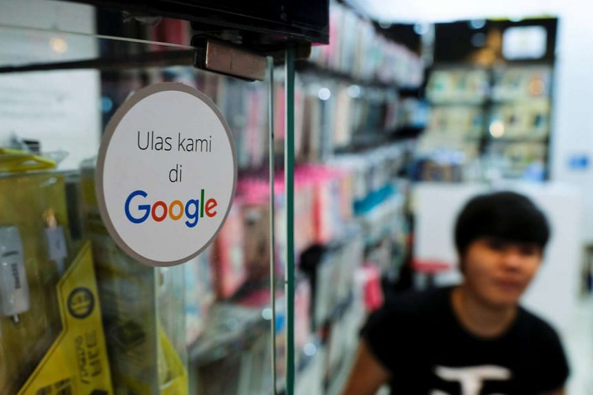 A sticker reading 'Review us on Google' is pictured at a smartphone shop in Ambassador Mall in Jakarta.