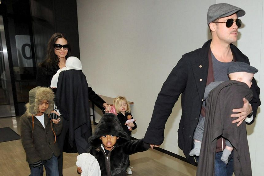 US actor Brad Pitt with his son Knox (in arms), daughter Zahara (left) as his partner, US actress Angelina Jolie holds their daughter Vivienne and son Maddox (left) and daughter Shiloh (right) at Tokyo's Narita International Airport in Japan.