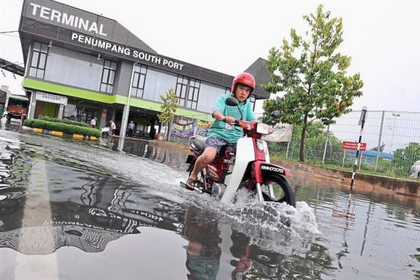 A motorcyclist riding through a flooded stretch of road in front of the Pulau Ketam jetty in Port Klang.