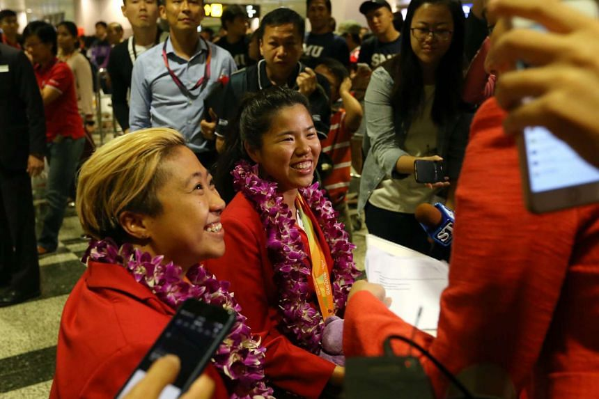 Singapore's Paralympians including Theresa Goh (left) and Yip Pin Xiu (centre) after arriving at Changi Airport.