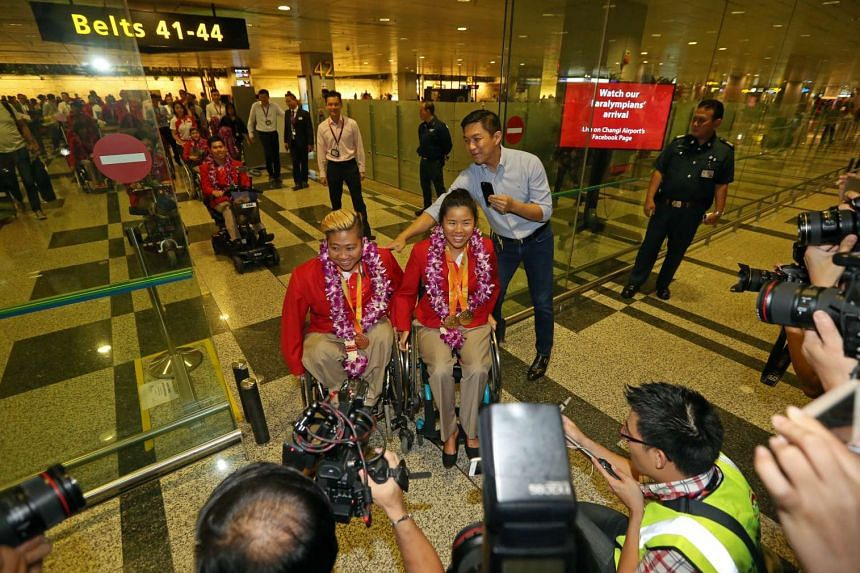 Singapore's Paralympians including Theresa Goh (left) and Yip Pin Xiu  who were welcomed by Minister Tan Chuan-Jin, family, friends, supporters and sports officials at Changi Airport on Sept 21.
