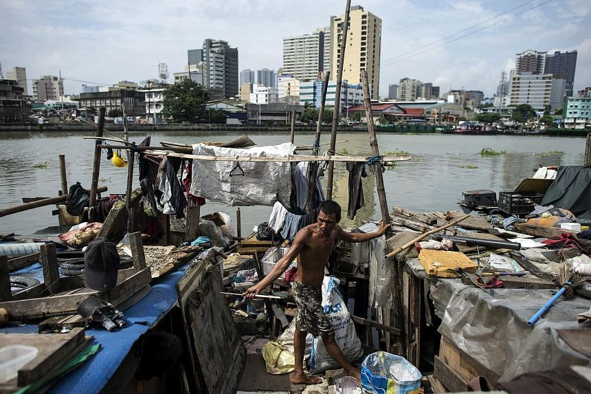 A man is seen in his house at the banks of the Pasig River in Manila on Aug 19, 2016.