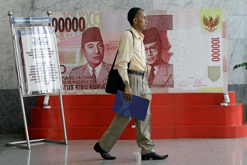 A man walks past a poster of a one hundred thousand rupiah bank note at Bank Indonesia, in Jakarta, Indonesia, on July 21, 2016.