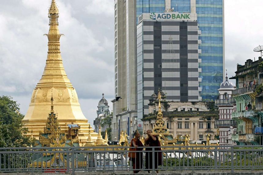 Buddhist monks stand on a bridge near the Asia Green Development Bank (AGD Bank) in downtown Yangon, Myanmar.