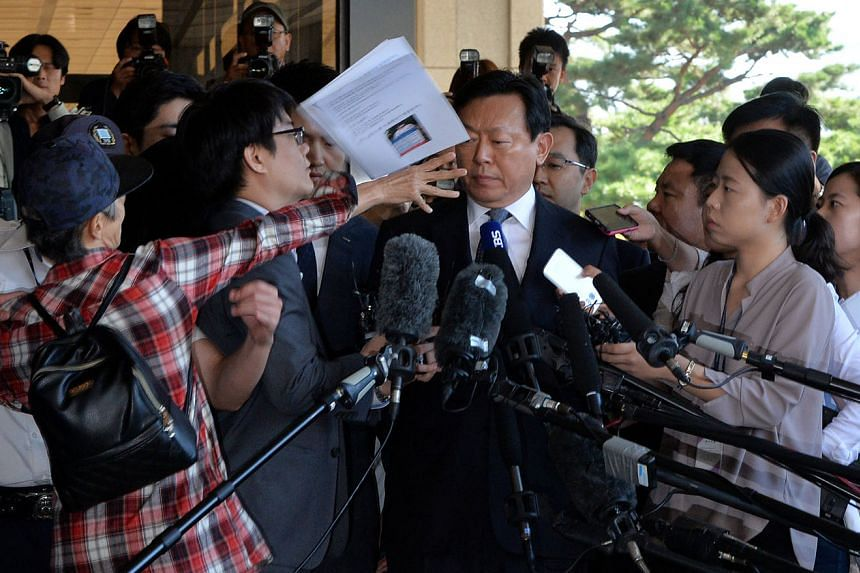 An unidentified man hurling documents at Lotte Group chairman Shin Dong Bin upon his arrival to the prosecutor's office in Seoul yesterday.