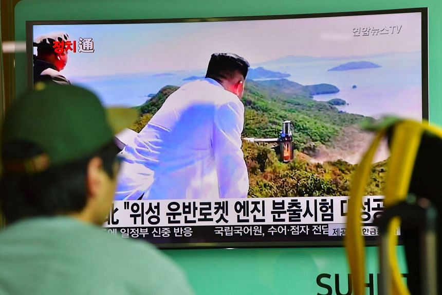A TV news report showing North Korean leader Kim Jong Un looking at the country's latest ground test of a rocket engine yesterday.