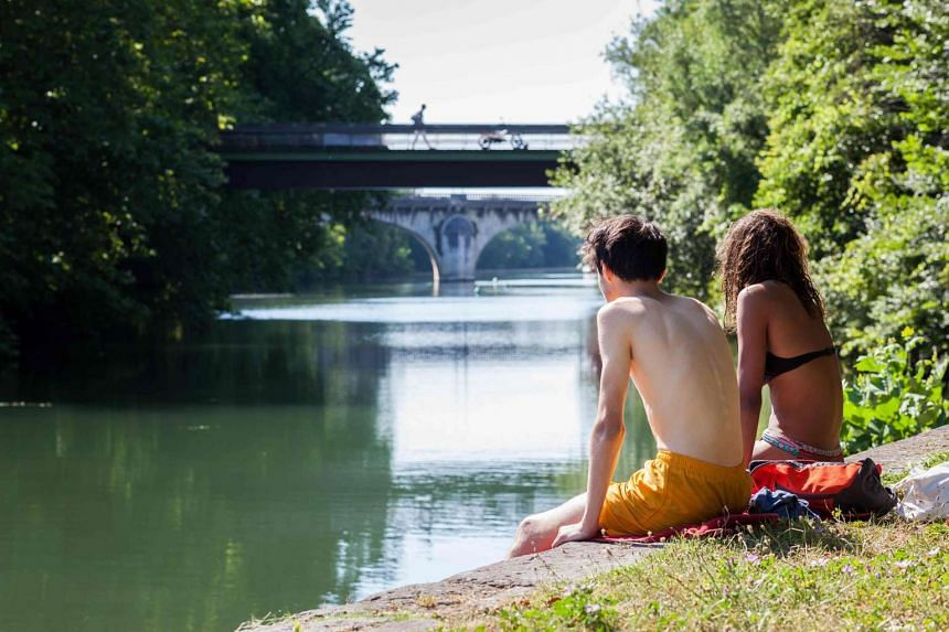 Two teenagers sit on the edge of the Charente canal in Angouleme, France, on July 19, 2016.