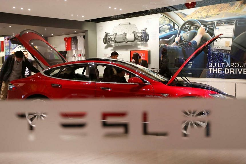 A man looks at a Tesla Motors' Model S P85 at its showroom in Beijing.