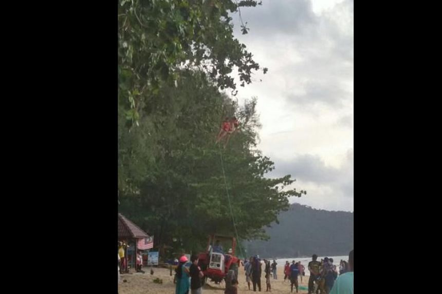 Operators trying to rescue the two tourists who got caught among the pine trees in Batu Ferringhi, Penang on Sept 19, 2016.
