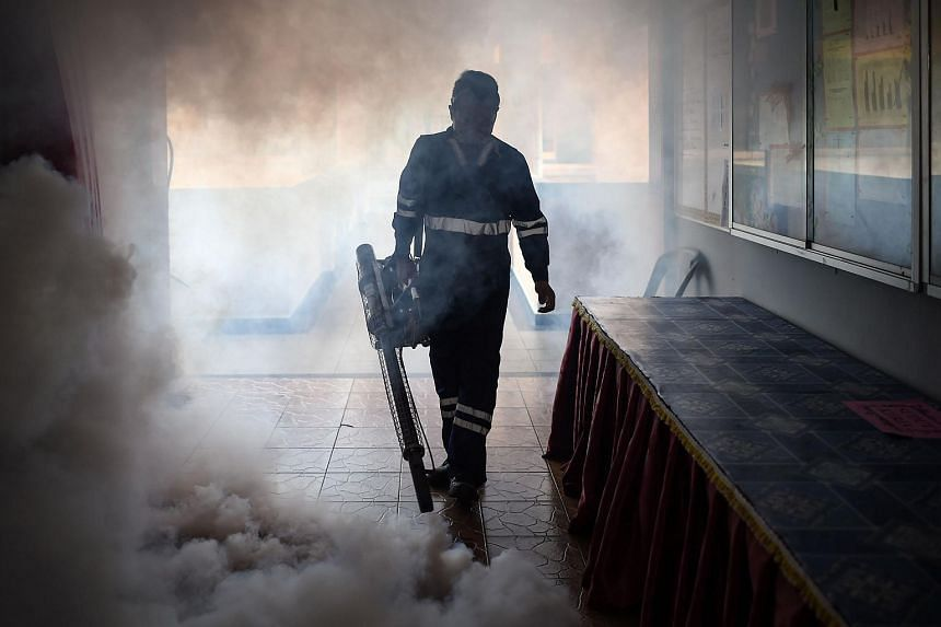 A pest control worker fumigates a school classroom in Malaysia on Sept 4, 2016.