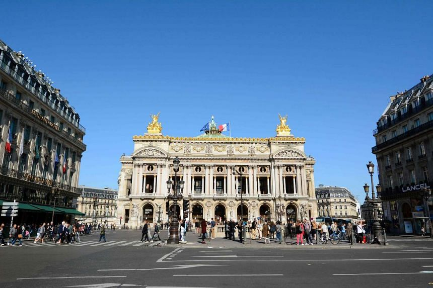 """People walk outside the Palais Garnier opera house during the """"Car-Free Day"""" event in Paris in 2015."""