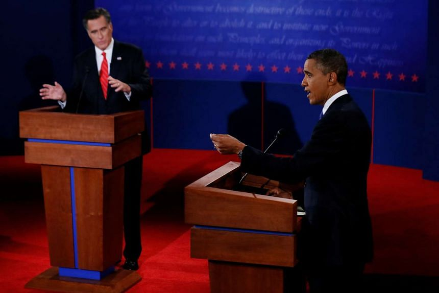 President Barack Obama answers a question as Republican presidential nominee Mitt Romney listens during the first 2012 US presidential debate in Denver on Oct 3, 2012.