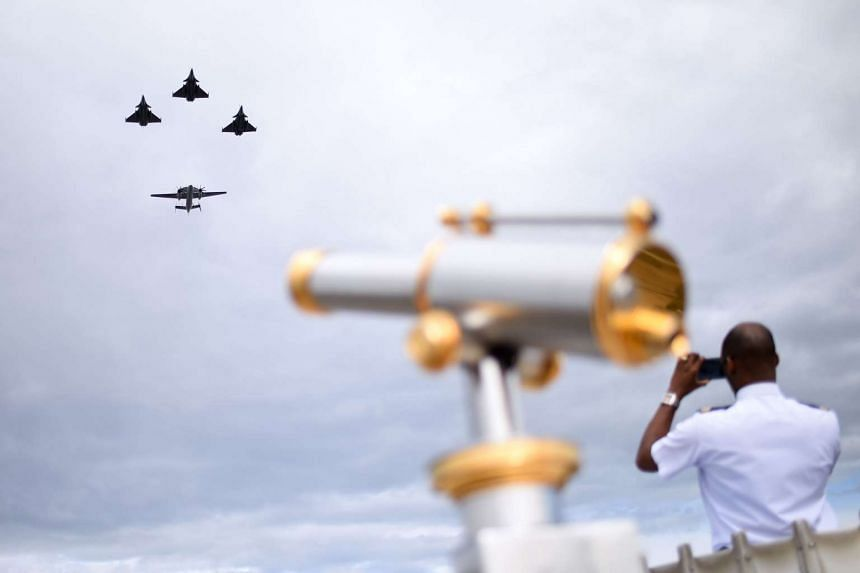 Rafale M fighter jets fly ahead of an E2C during the annual Bastille Day military parade in Paris on July 14, 2016.