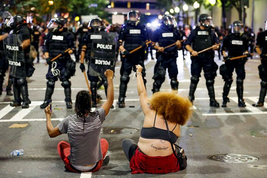 Two people sit on the ground as they protest in front of police in uptown Charlotte, North Carolina, during a protest of the police shooting of Keith Scott, on Sept 21, 2016.