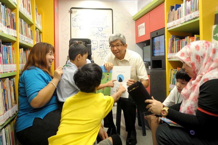 Associate Professor Dr Yaacob Ibrahim (second from right) reading a book titled Shark in the Park to the students inside the new Molly.