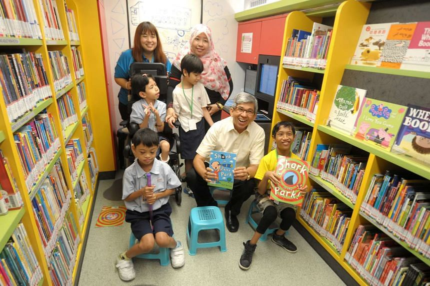 Associate Professor Dr Yaacob Ibrahim (second from right), Minister for Communications and Information and Minister-in-charge of Muslim Affairs, inside the new Molly with Associate Librarian, Ms Lee Siew Ting (top left), 27, Ms Nurfadzlin, 37, teache