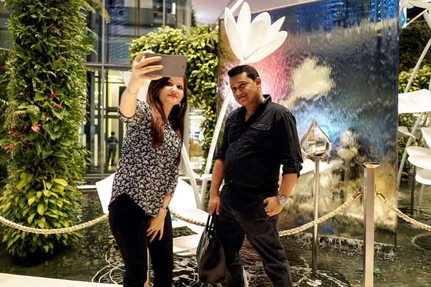 Tourists take a selfie at a department store in Bangkok.