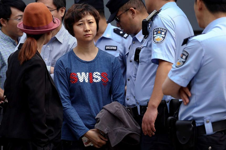 Police stand around Lin Ru, the wife of civil rights lawyer Xia Lin, near the Beijing Number 2 People's Intermediate Court after her husband was sentenced to 12 years in prison on fraud charges. in Beijing on Sept 22, 2016.