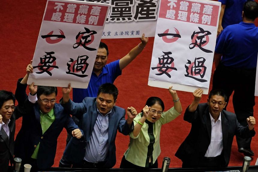 """Legislators from the ruling Democratic Progressive Party displaying placards reading """"ill gotten party assets bill must pass"""", inside the parliament in Taipei on July 22, 2016."""