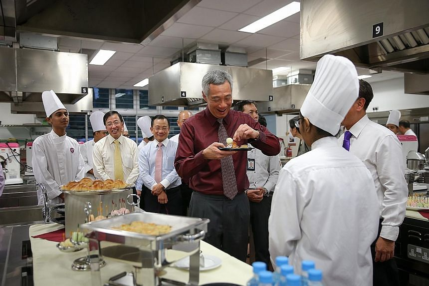 PM Lee sampling pastries made by NorthLight students yesterday. The school has changed not just the lives of its students, but has also influenced Singapore's wider education system, he said.