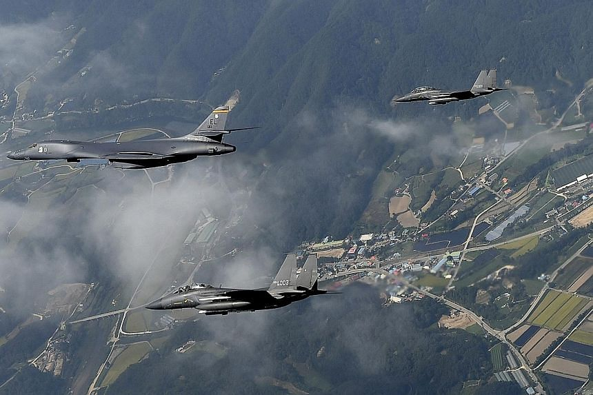 A US B-1B Lancer bomber, flanked by two South Korean F-15K fighters, flying over Osan Air Base, south of Seoul, in a handout photo released by the South Korean Air Force yesterday. The flight came a day after Pyongyang claimed it had successfully tes