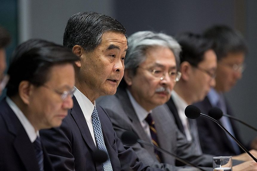 Mr Leung (second from left) and Mr Tsang (third from left) at the press conference yesterday where they faced questions from reporters over their links with a troubled public housing development.