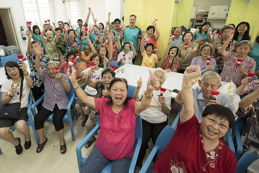 Participants from the Awwa Senior Activity Centre holding up the Samsui women dolls they made with staff volunteers from SGX last month.