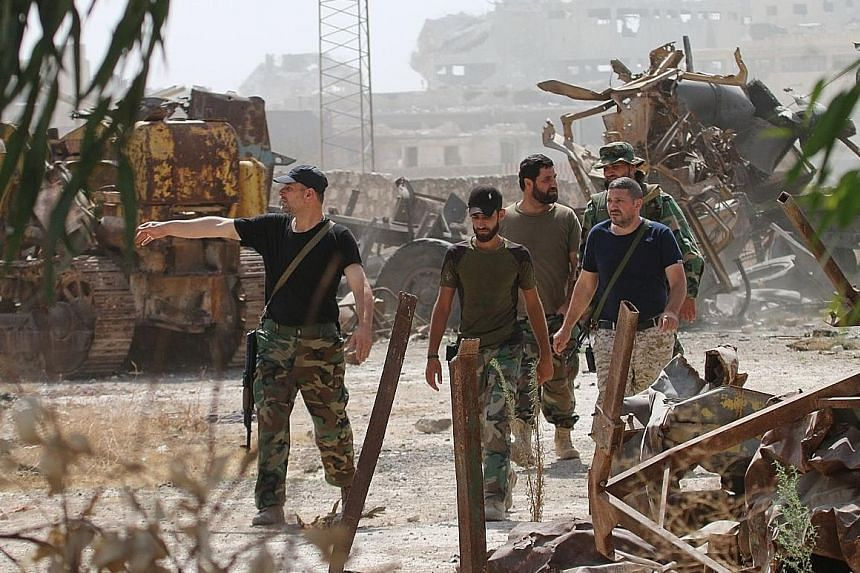 Syrian pro-regime fighters patrolling the Ramousah area, south of the city of Aleppo, yesterday. Syrian state media and a television station controlled by its Lebanese ally Hezbollah said that the army had recaptured a fertiliser factory in the Ramou