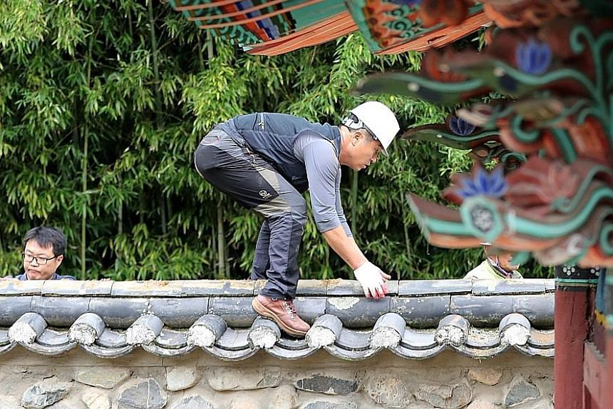 Workers from a cultural property repair agency replacing roof tiles at a traditional building in the city of Gyeongju, South Korea, on Sept 19 - a week after a 5.8