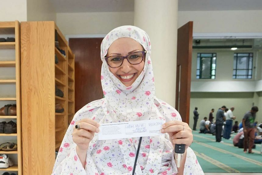 Ms Nahid Jalali, a 47-year-old masters student, proudly holding a Virginia voter registration application receipt.