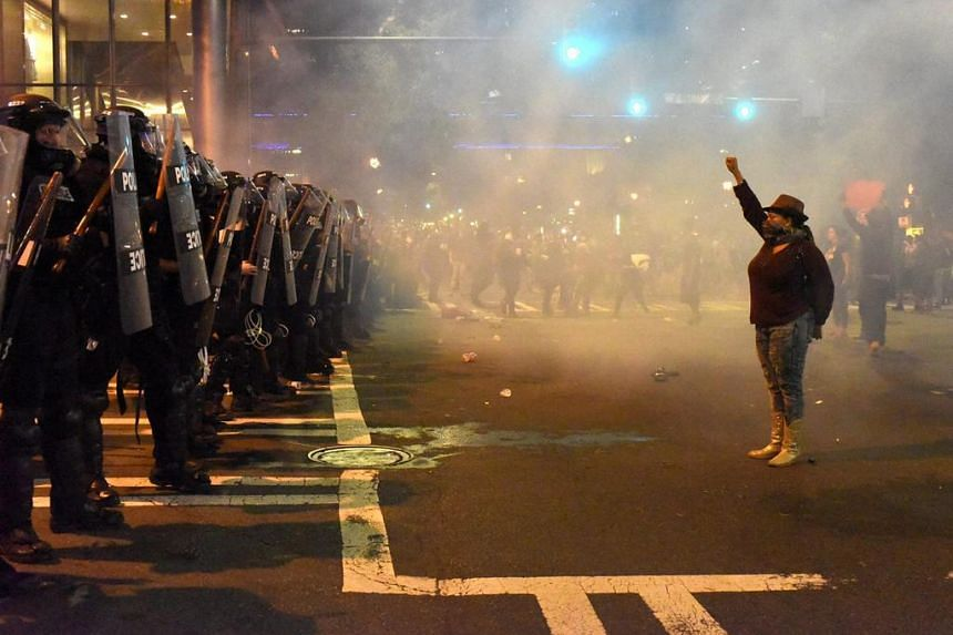 A protester stands with her fist raised as she confronts police officers in Charlotte, North Carolina on Sept 21, 2016.