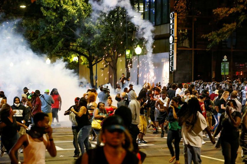 People run from flash-bang grenades in uptown Charlotte during a protest of the police shooting of Keith Scott, in North Carolina on Sept 21, 2016.