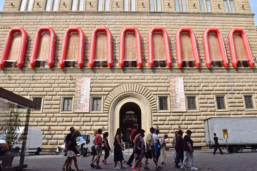 Red inflatable lifeboats are attached to the windows of Palazzo Strozzi's facade for the Ai Weiwei Libero exhibition in Florence.