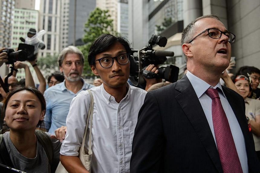 Hong Kong lawmaker Eddie Chu (centre) arriving at Wanchai Police Station to make a report on Sept 8, 2016, after receiving death threats allegedly from people with links to the city's triads.