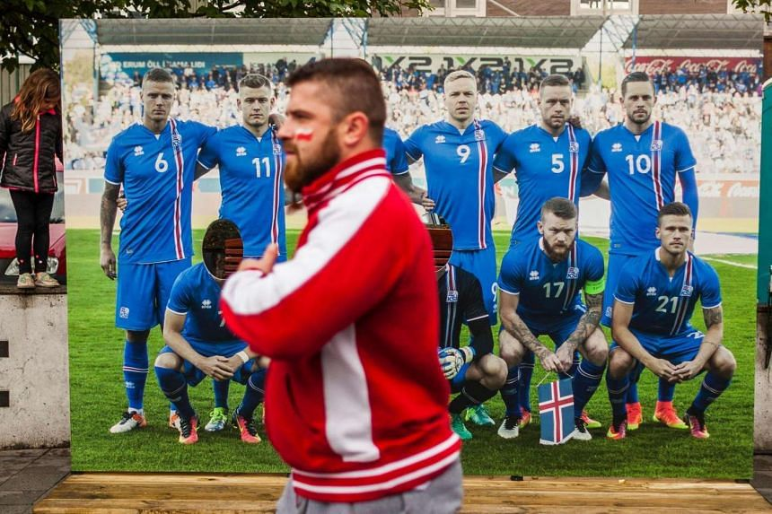 A Polish fan passes by a picture of the Icelandic football team in Reykjavik, on June 30, 2016.