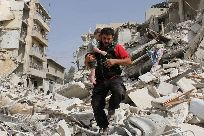 A Syrian man carries a baby after removing him from the rubble of a destroyed building following a reported air strike in the Qatarji neighbourhood of Aleppo on Sept 21, 2016.