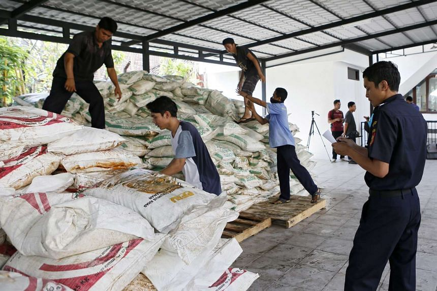Indonesian workers unload sacks of ammonium nitrate that was illegally imported from Malaysia at a customs office in Denpasar, Bali on Sept 22, 2016.