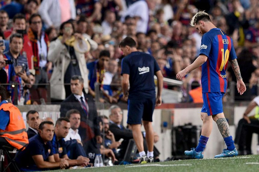 Barcelona's Argentinian forward Lionel Messi leaves the pitch after being injured.