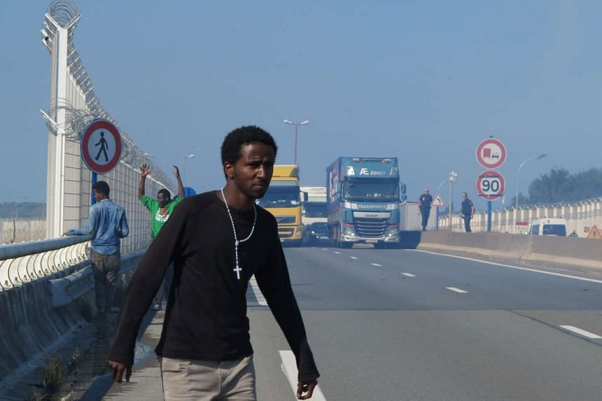 Migrants walk near lorries which are heading towards the ferry terminal in Calais, France, Sept 21, 2016.