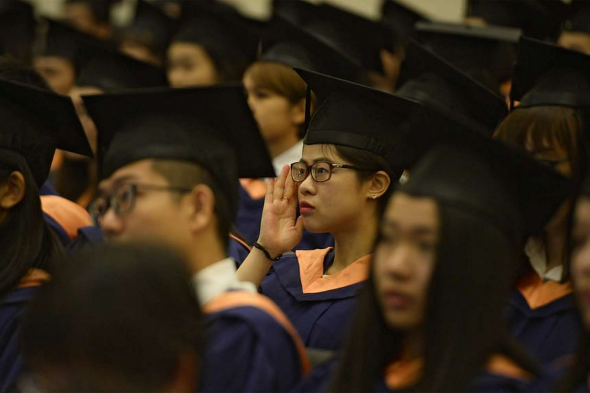 A graduate adjusting her glasses as she listens to a speech at the National University of Singapore (NUS) Commencement ceremony.