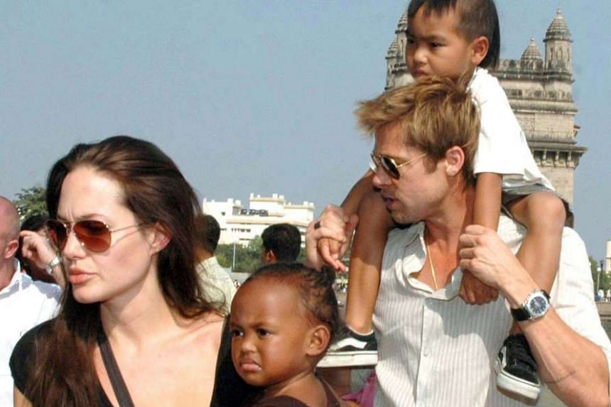 Jolie holding daughter Zahara and Pitt carrying son Maddox in Mumbai, India, in 2006.