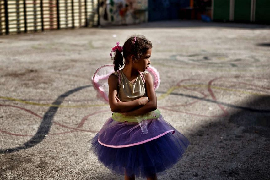 A young girl stands in the courtyard of an abandoned school used by volunteers for hosting Syrian and Afghan refugees in Athens on July 1, 2016.