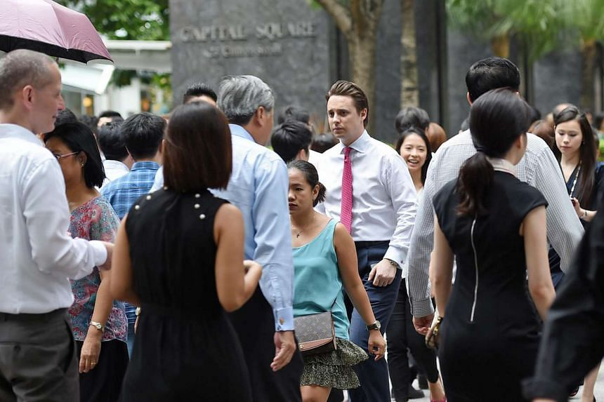 Office workers during lunch time at a pedestrian crossing along Church Street at Raffles Place on June 16, 2014.