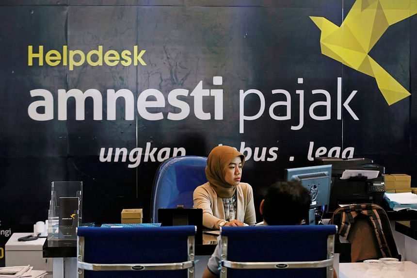 An officer assists a tax amnesty participant at the country's tax headquarters in Jakarta, Indonesia on Sept 8, 2016.