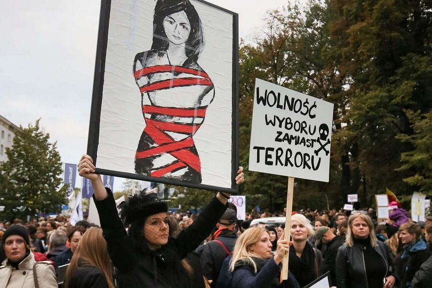 """A protester holds a banner with slogan reading """"'Freedom of choice not the terror"""" in Poland on Sept 22, 2016."""